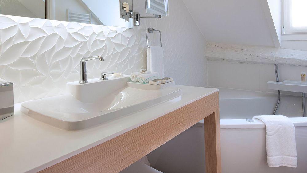 Design, cette salle de bains blanche avec baignoire, miroir