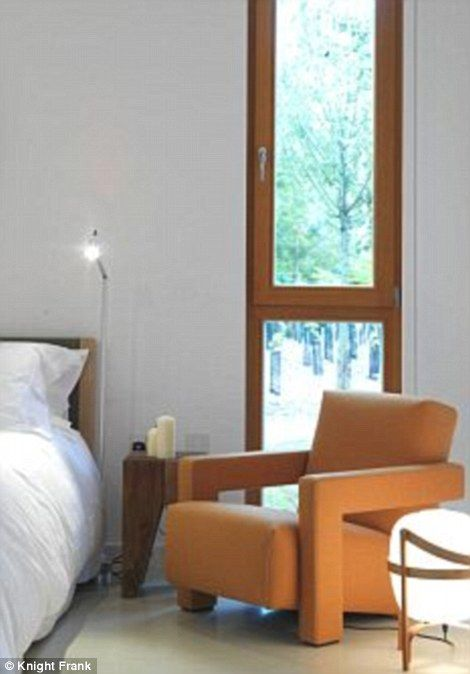 A glimpse of the bedroom's mid-century style furniture and ceiling high windows