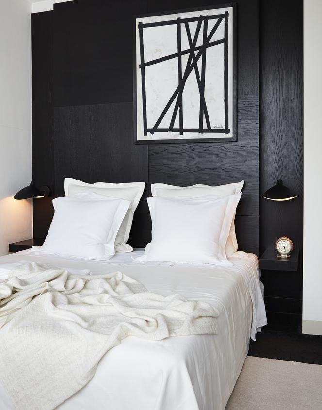 Ook de slaapkamer is in zwart-wit. Aan het voeteneind van het bed ...
