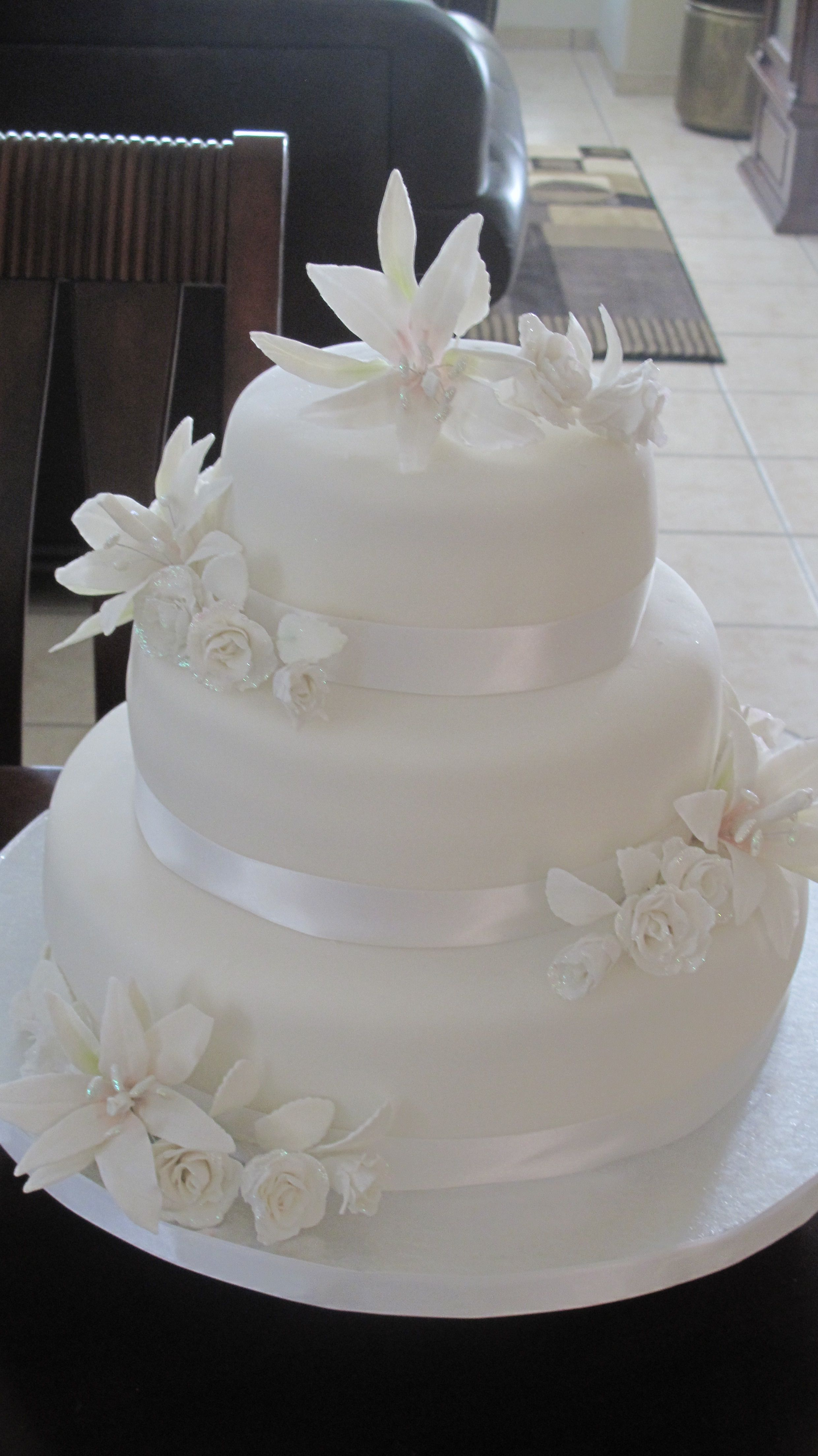 An anniversary cake adorned with gumpaste lilies roses and satin