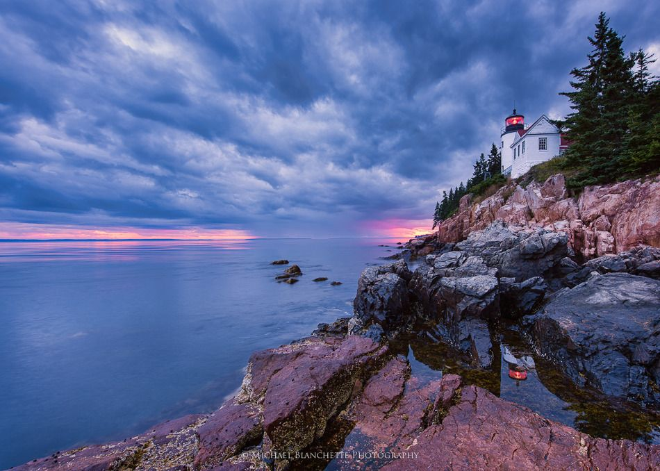 Bass Harbor Head Light is located within Acadia National Park, on the southwestern side of Mount Desert Island, Maine. The brick lighthouse was built in 1858, and sits on a cliff some 56' above high water of the Atlantic. This photo was taken at sunset, as the sun went down directly behind the lighthouse. Beacon Reflection by Michael A Blanchette | Earth Shots