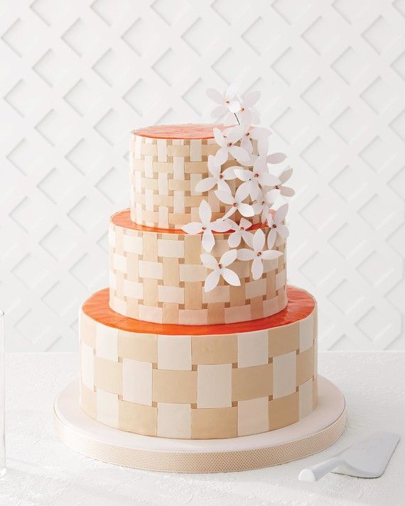 """This clever gum-paste """"picnic basket"""" is a modern take on old-school basket-weave buttercream. The extra stroke of brilliance? A glassy layer of apricot glaze atop each tier, which complements the almond cake beneath and adds beautiful color. MSW contributing editor Jason Schreiber covered the cake with tinted fondant before adding the strained jam, taking the friendly orange hue up to electrifying. Canvas flowers pressed into the lattice make for an ever prettier finish.    The De..."""