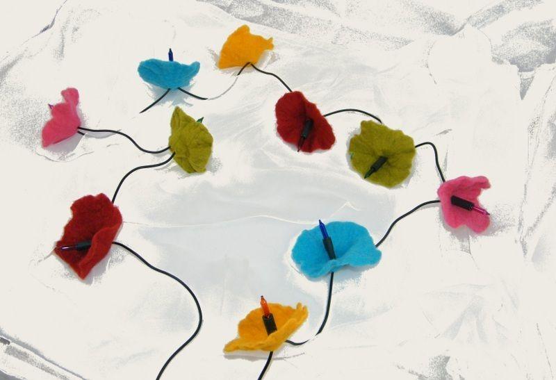 An einer grünen Lichterrkette ohne Schalter ranken sich 10 bunte Blüten. Die Glühbirnen der Lichterkette leuchten auch bunt.    Jede einzelne ...