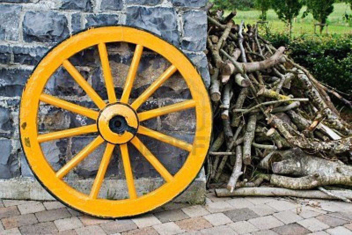 An old antique yellow wooden wagon wheel leaning against a stone ...