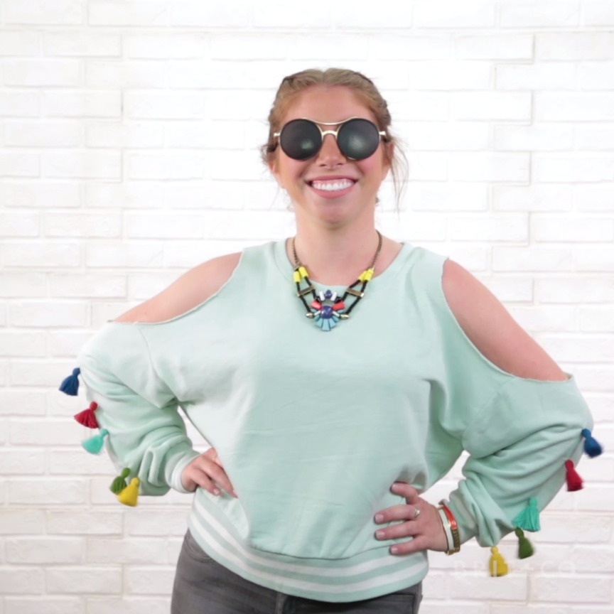 Watch this style DIY video tutorial to learn how to make a cold shoulder tassel sweater top.