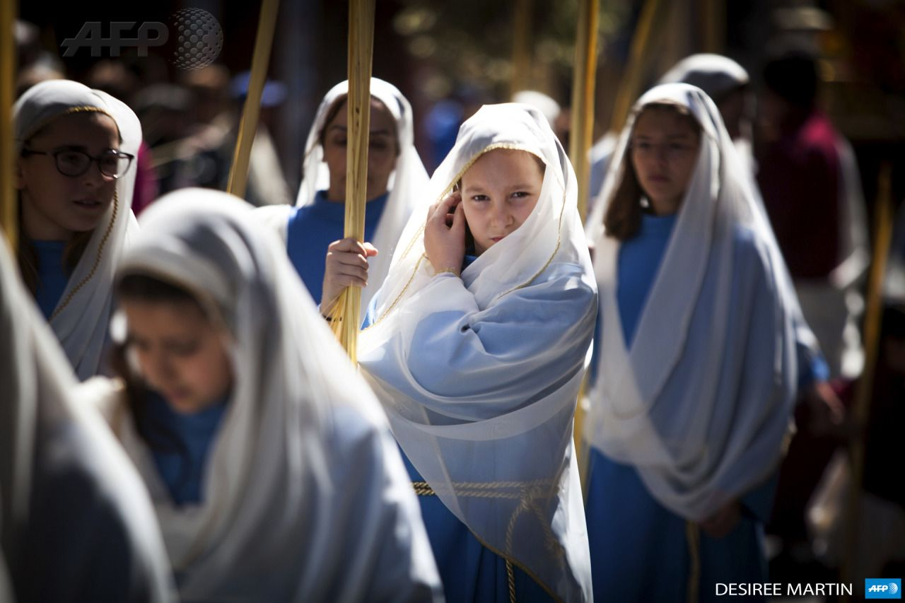 SPAIN, LA LAGUNA : Girls hold palm leaves blessed during the morning Mass at the Cathedral of San Cristobal de La Laguna during a procession  commemorating the arrival of Jesus in Jerusalem, on the Spanish Canary  island of Tenerife on March 29, 2015.  Palm Sunday held annually on the  Sunday before easter and commemorates the entry into Jerusalem of Jesus  Christ. AFP PHOTO / DESIREE MARTIN