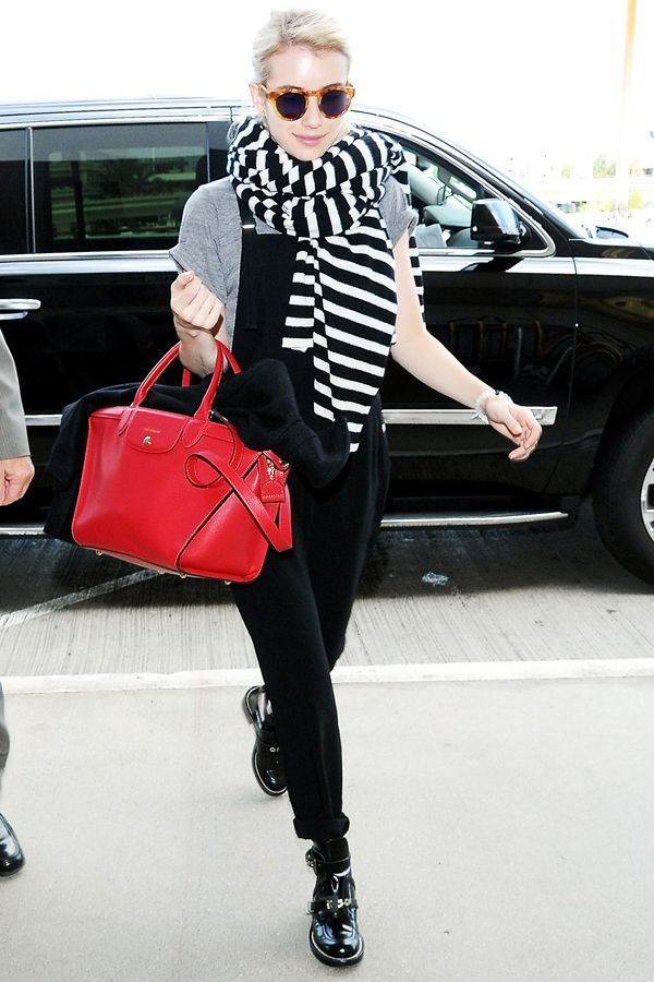 Emma Roberts was photographed at the airport in Elizabeth and James overalls, a black-and-white striped scarf, and buckle-strap ankle boots by Balenciaga — a.k.a. the coolest travel shoes around.