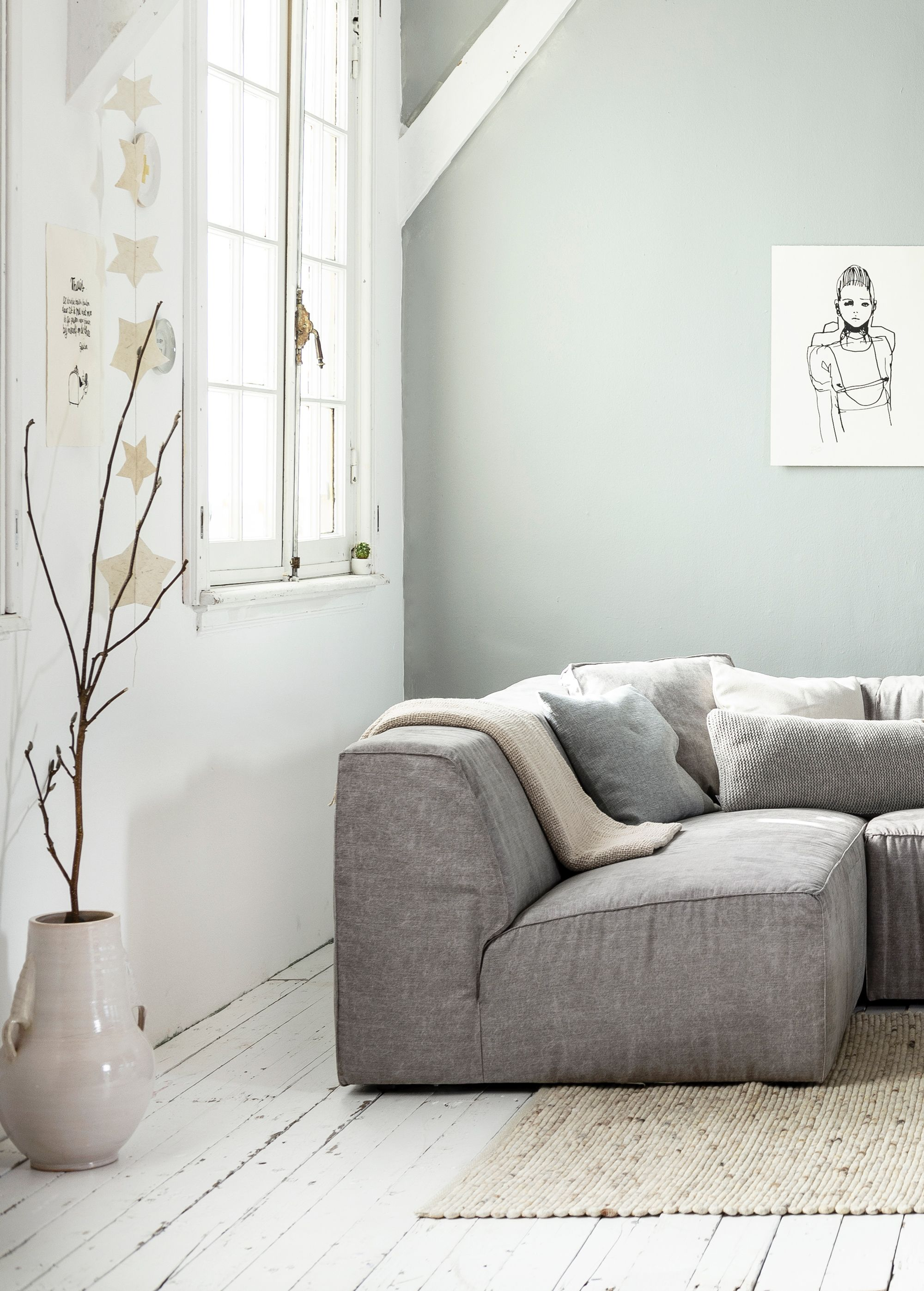 white grey and light interior living room with white wooden floors and a grey wall grey canvas vtwonen couch lazy a big off white vase by nijhof