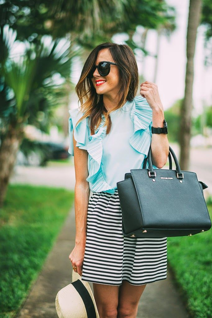 Blue pastel ruffle blouse, black and white striped skirt, and black tote.