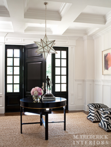 This is an inspiration for a classic-inspired foyer with round table at the center with decorations serving as centerpieces. The dark-tone colored table and front door blend with the white wall and coffered ceiling. The painting and the zebra-inspired stools are add significant beauty to the setting.