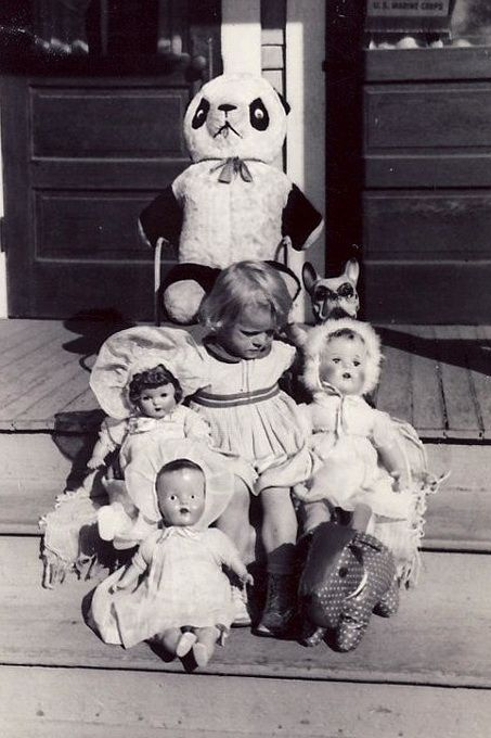 1950s blonde haired girl with her dolls, large panda, and toys.