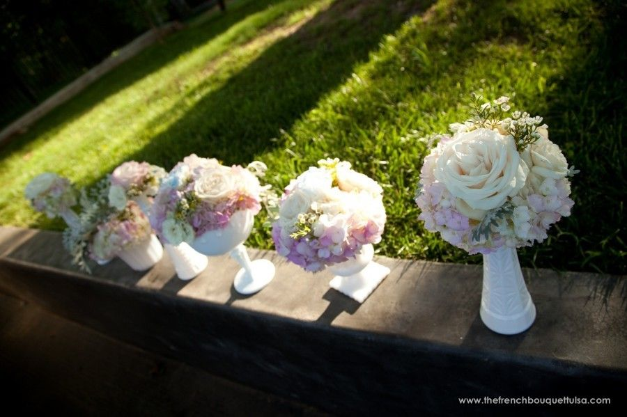 creams and light purple vintage centerpieces in white milk vases