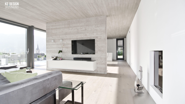 offenes Wohnzimmer mit Sichtbetonwand und Decke in Brettschaloptik ...