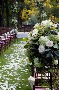 The entrance to a petal-strewn aisle is marked with a pomander of hydrangeas, white roses and seedpods.