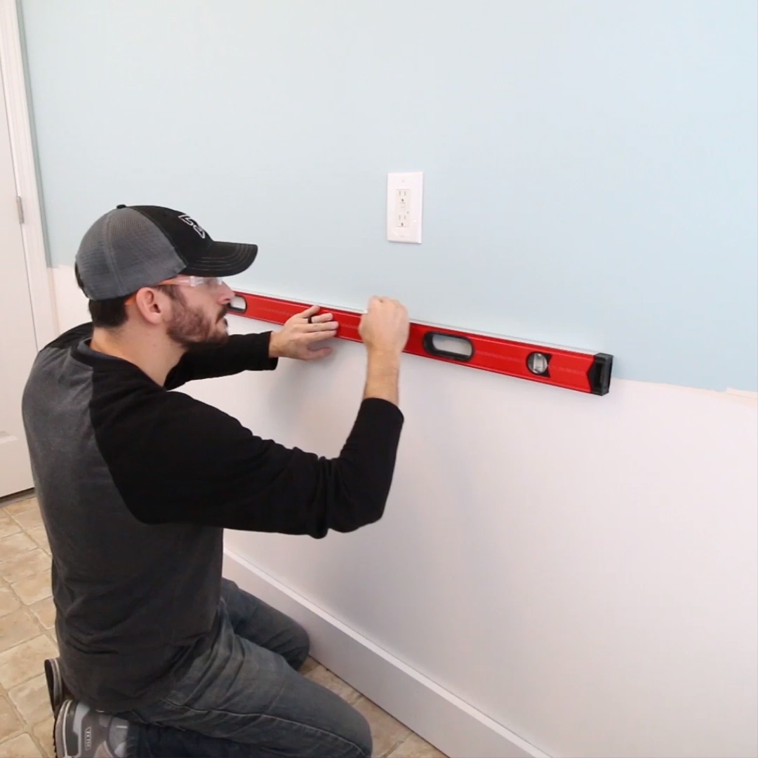 Learn how to install wainscoting with a board and batten look. This DIY home improvement project is great to upgrade a living room, dining room, or put in a laundry room like we did. Installing a board and batten wall is pretty easy with the right tips and tricks! #wainscoting #boardandbatten #boardandbattenwall #laundryroomideas