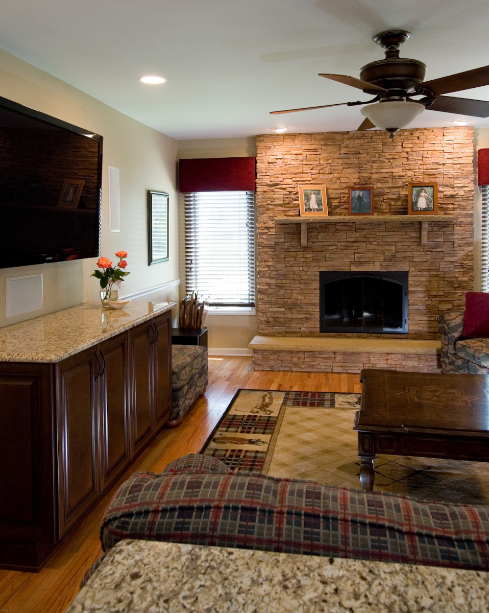 NDA Kitchens - Living Room, stone fireplace, TV above granite countertop/ wood cabinets
