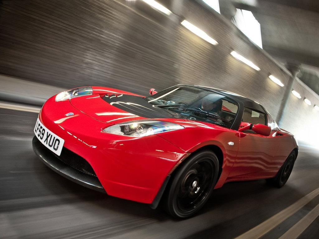 Red tesla roadster speeding through a tunnel for more check out www