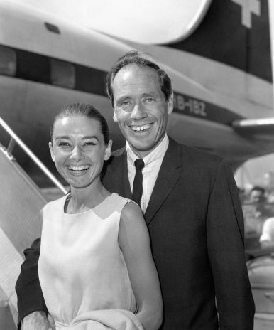 The actress Audrey Hepburn photographed with her husband Mel Ferrer during their arrival at the Heathrow Airport in London (England), from Zurich (Switzerland), for the premiere of her latest film...