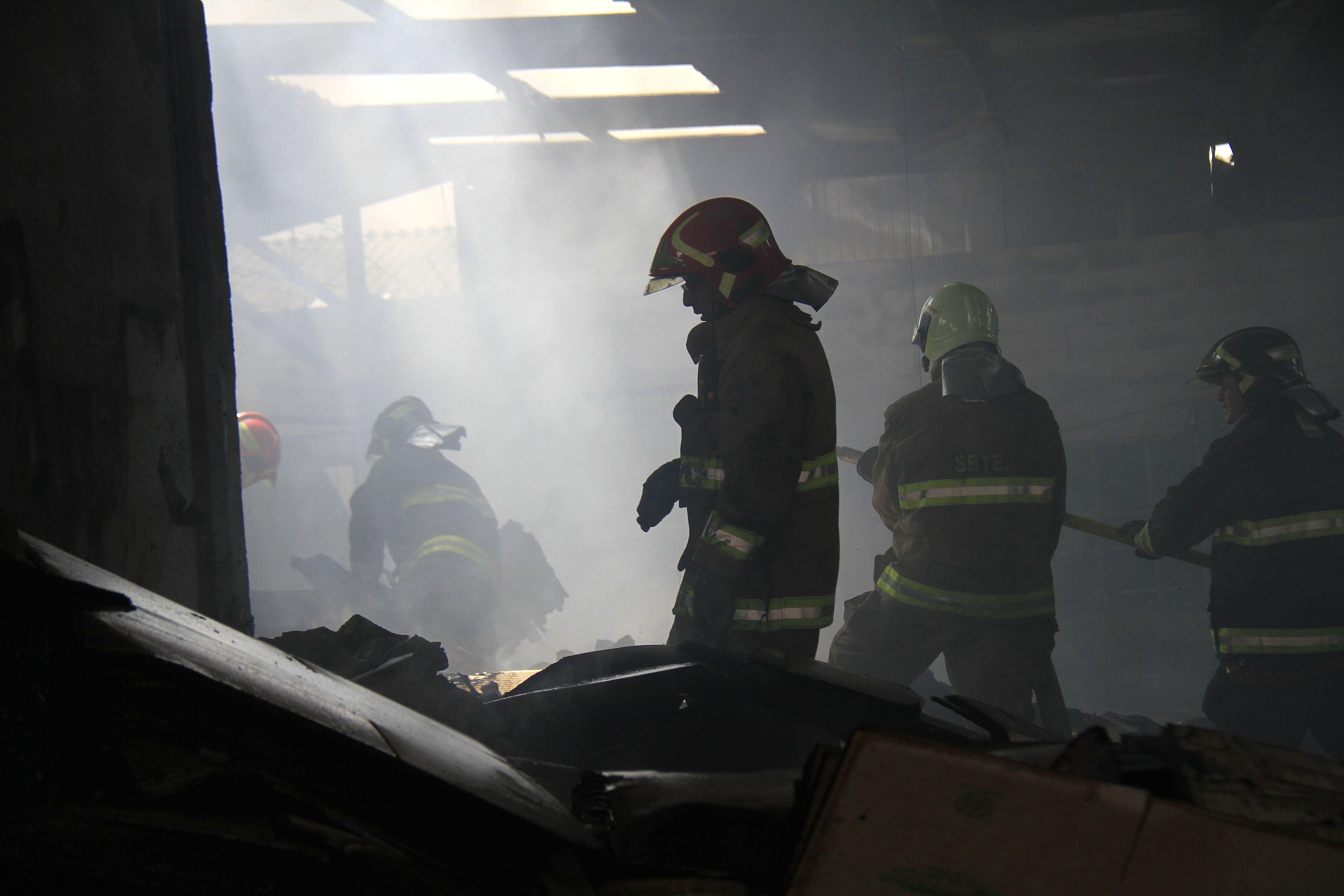 Bomberos inspeccionando el lugar luego del incendio.