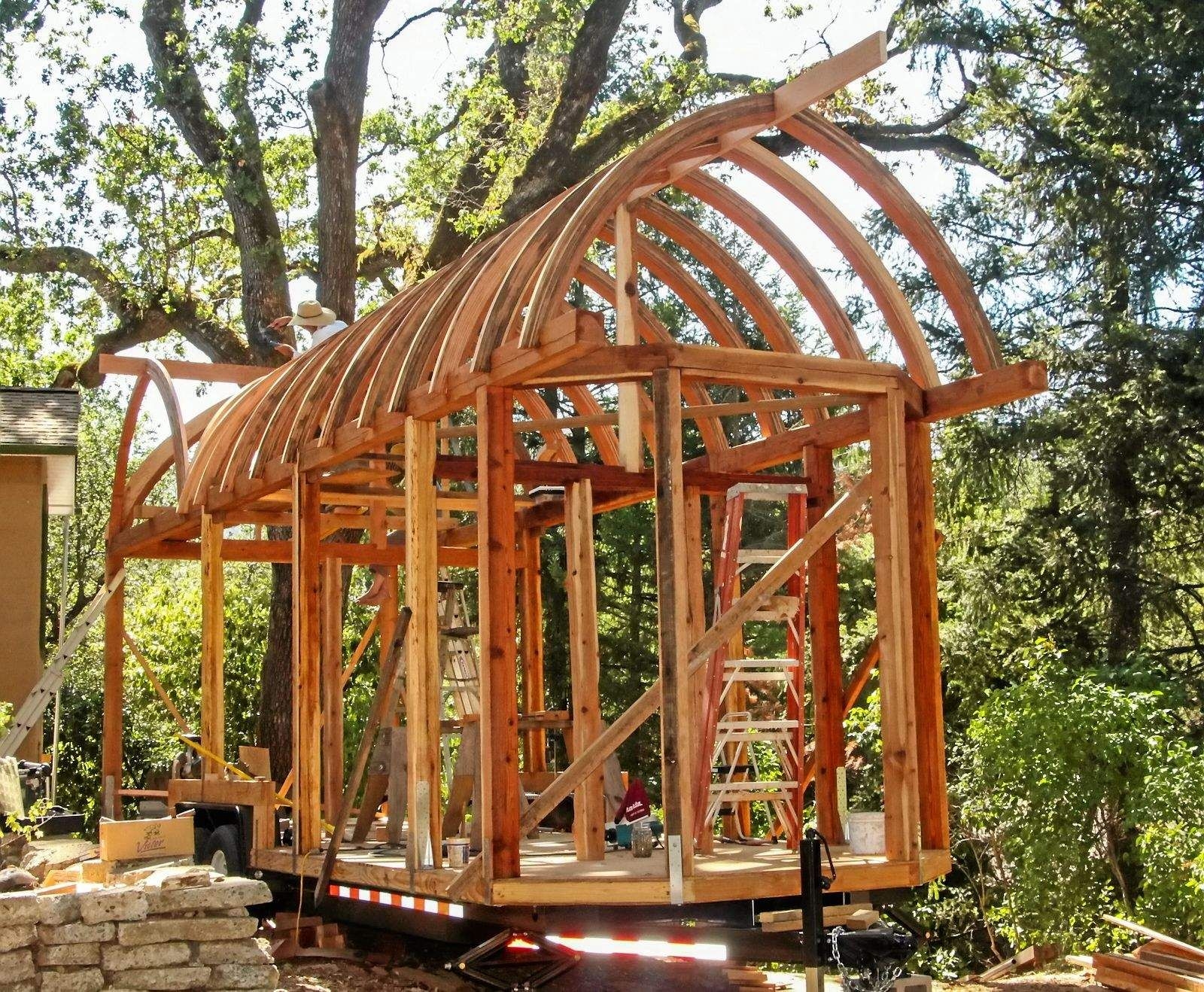 Curved roof tiny house under construction incredible for Small home construction plans