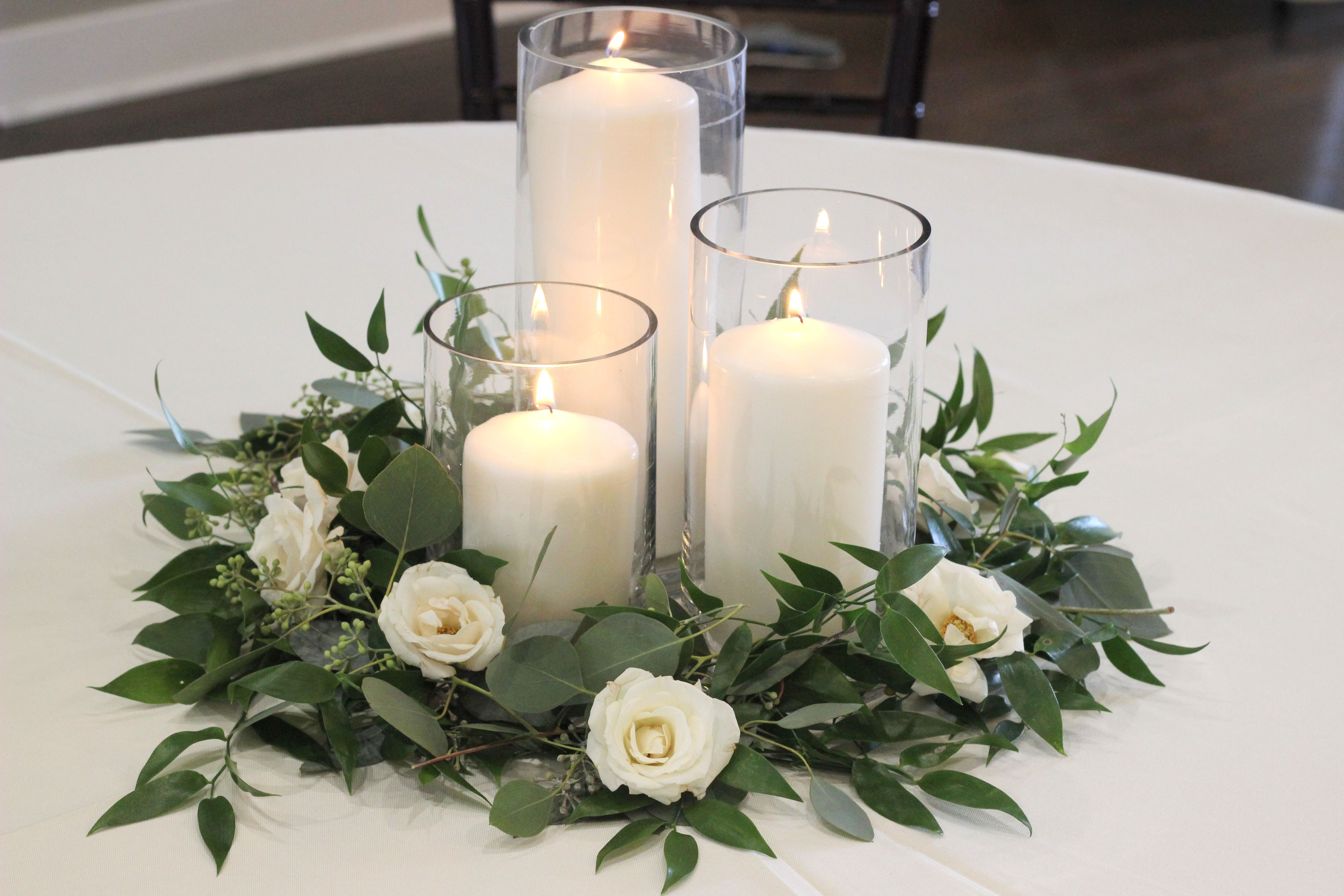 Greenery And Spray Rose Centerpiece With Pillar Candles Celebration Flair Candle Wedding Centerpieces Wedding Table Centerpieces Rose Centerpieces