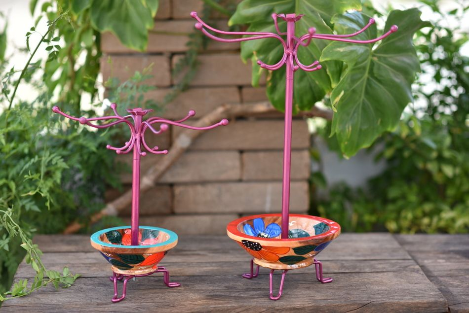 Large and small jewelry stands with metal hooks to hang necklaces and a bowl at the bottom to hold smaller jewelry pieces.