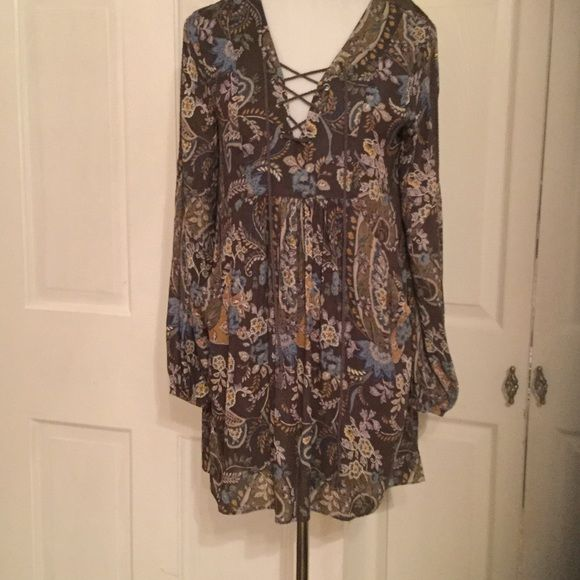 NWTFREE PEOPLE DRESS NWT FREE PEOPLE DRESS, smock mini dress.  Brown/grey back ground with blue and multi color floral design. Side pockets and tie front.  Free People Dresses Mini
