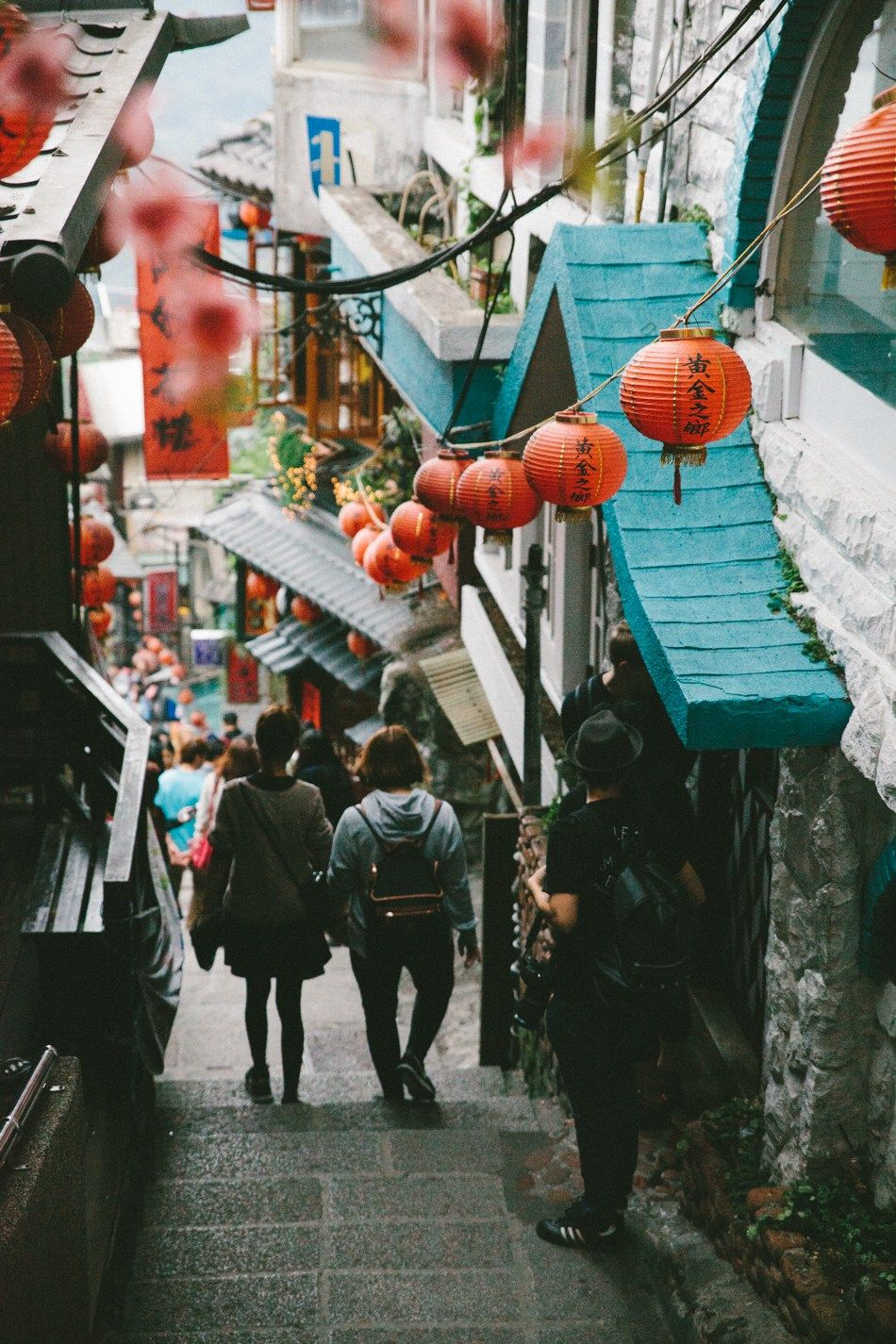 "This photo utilizes depth of field to bring us in towards the people walking, as well as line with the hanging lanterns to ""walk"" us through the picture with them."
