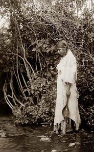Here we present a stunning image called Waters Edge. It was taken in North Dakota in 1908 by Edward S. Curtis.    The image shows a Young Arikara Indian Girl standing in shallow water, wearing a buckskin dress, with trees in background.    We have created this collection of images primarily to serve as an easy to access educational tool. Contact mailto:curator@ol....