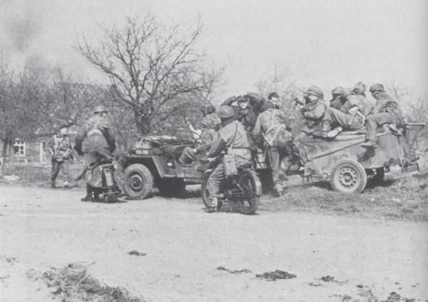 Men of the 12th Devons, with two prisoners in tow (centre, seated on the back of the Jeep), prepare to enter Hamminkeln