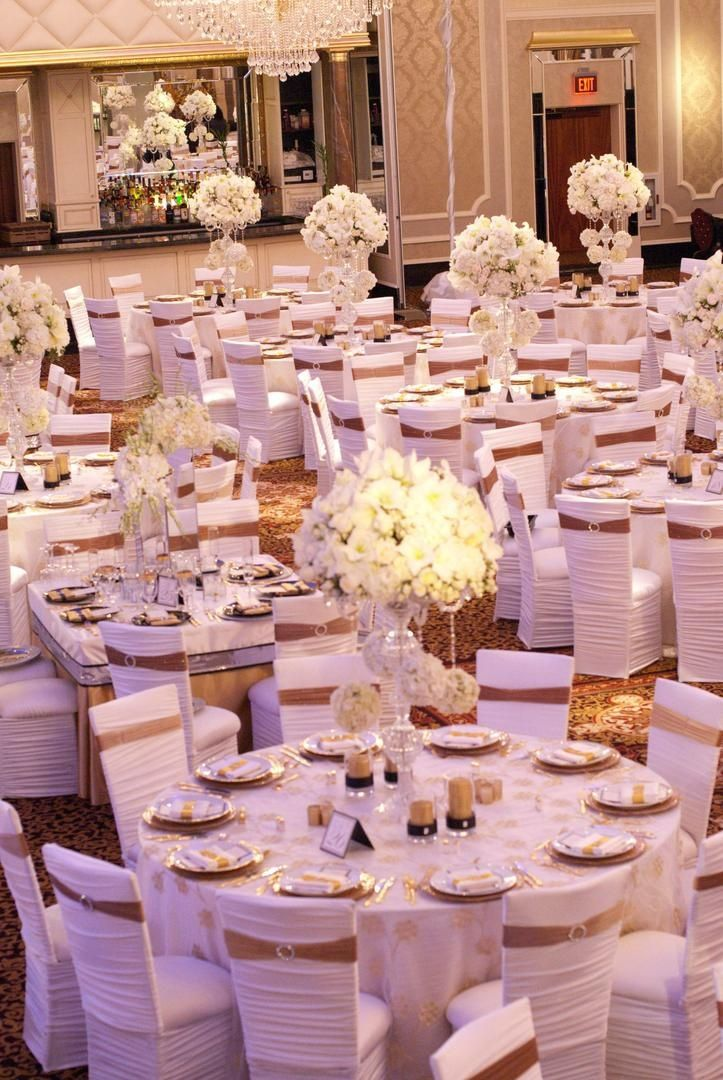 Wedding Reception With White Floral Arrangements And Chair Sleeves Gold Ribbons