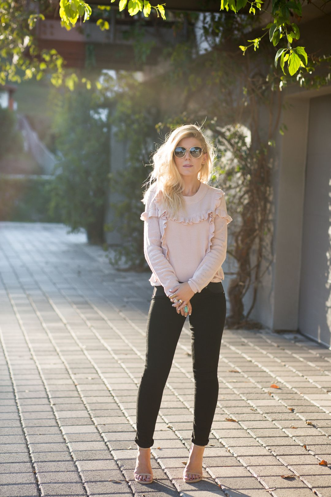 Lisa Allen of LunchPails and Lipstick wearing a pink ruffle sweater from Topsop with paige jeans and stuart weitzman heels