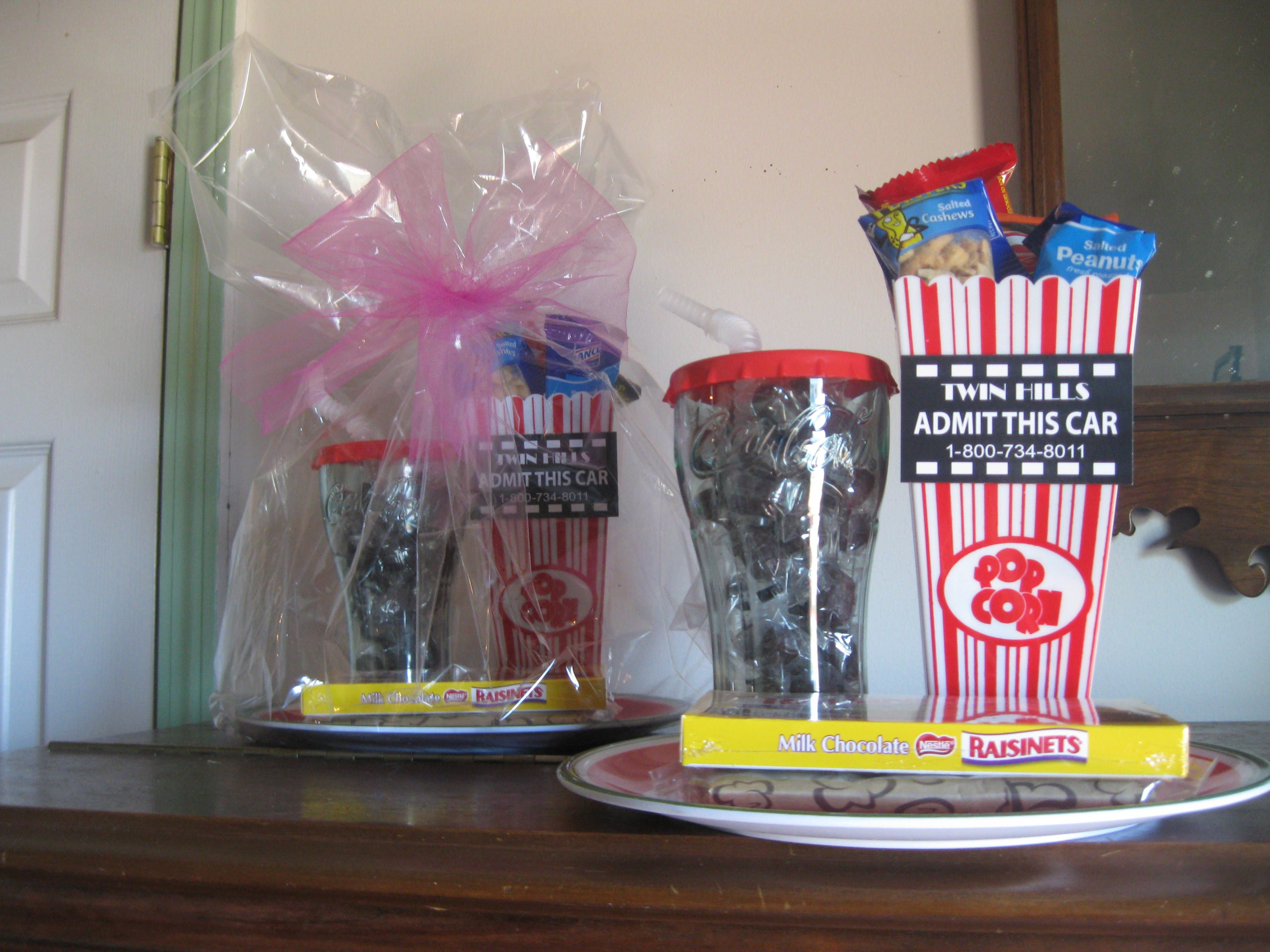 coca-cola plate with a coca-cola cup filled with root beer hard candy...a popcorn box with assorted mini candies, cookies, peanuts, and combos....a bag of microwave popcorn and large box of raisinettes in front...and a free pass to the drive-in or movie theater.