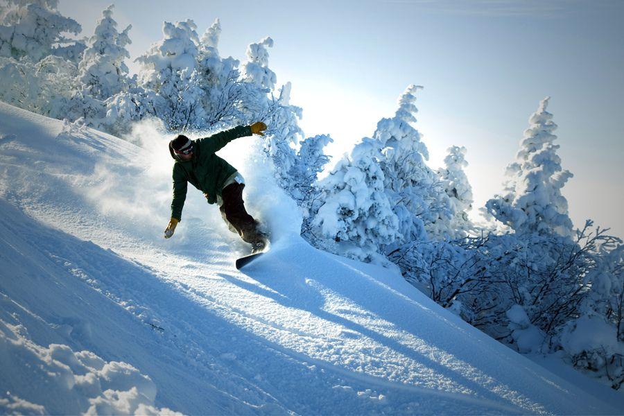 Blue sky day, powder turn on a Powderjet Snowboard. Snow