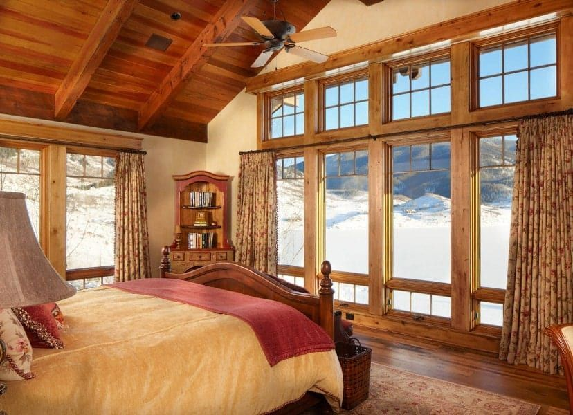 15+ Refreshing Master Bedroom Design Ideas for Renovation or Building #vaultedceilingdecor Rustic master bedroom featuring a tall vaulted ceiling with beams and hardwood flooring, along with glass windows. The room offers a nice bed lighted by table lamps. #vaultedceilingdecor