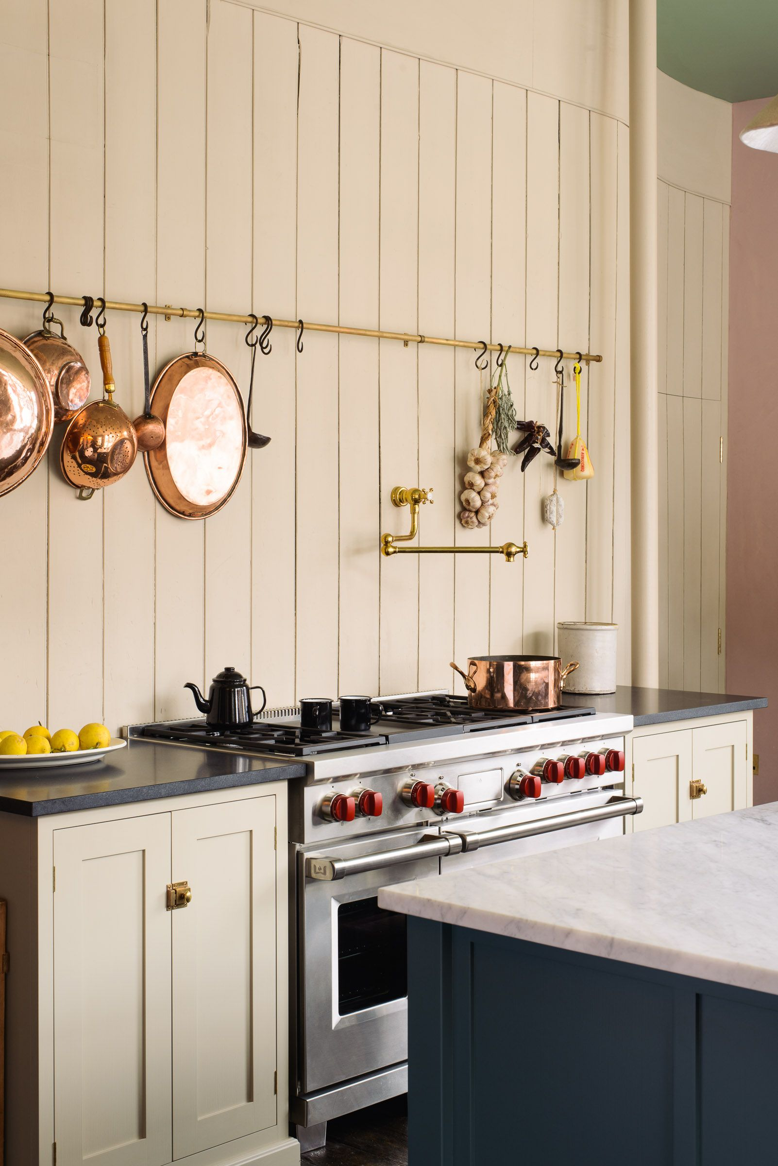 A brass hanging rail with copper pans, a deVOL pot filler and ...