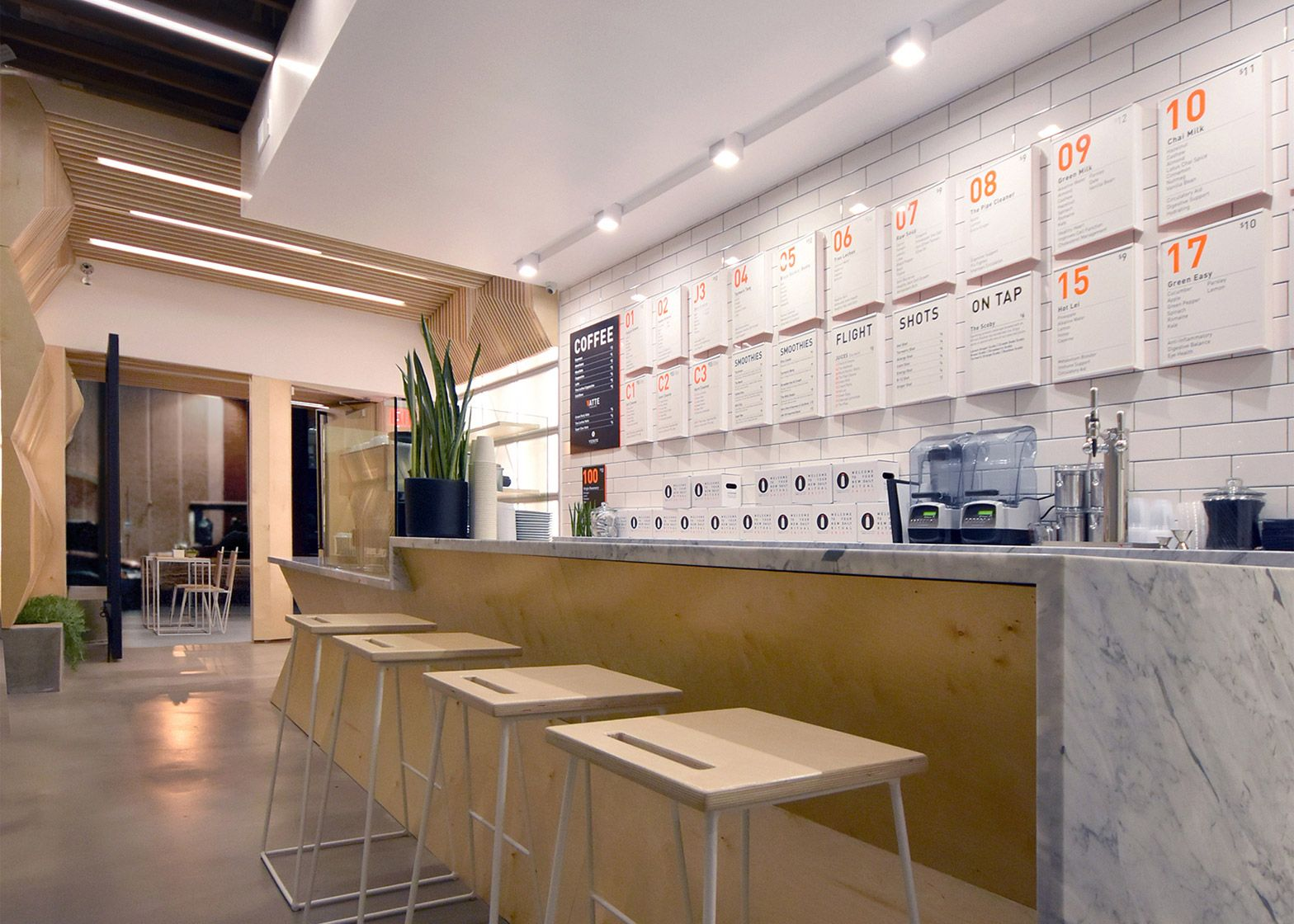 AIndustrial clads juice bar with geometric plywood hospitality