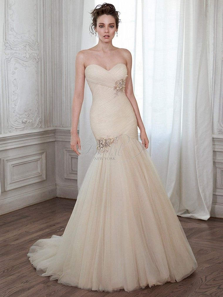 Lacey... A stunning fit and flare wedding dress featuring pleated tulle and flaring into a voluminous skirt, is complete with romantic sweetheart neckline and finished with corset closure. Available with optional detachable hand-embellished floral belt or attached hand-embellished floral motifs. Detachable belt sold separately.