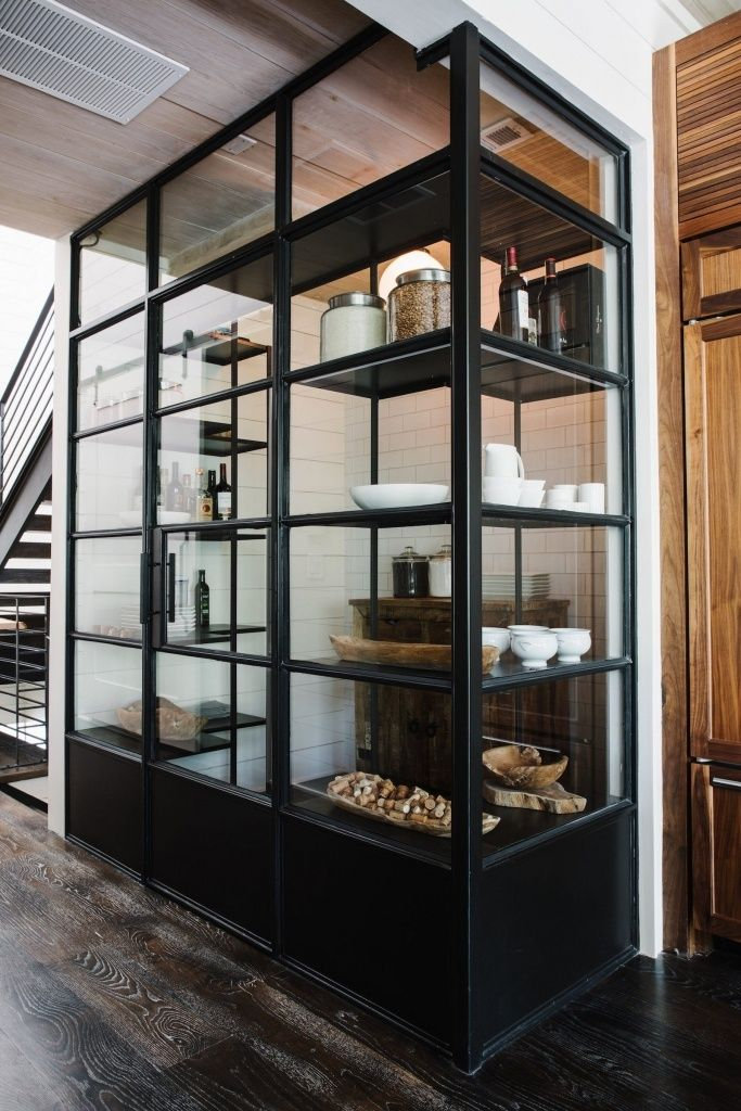 A steel-and-glass pantry is stocked with essentials.