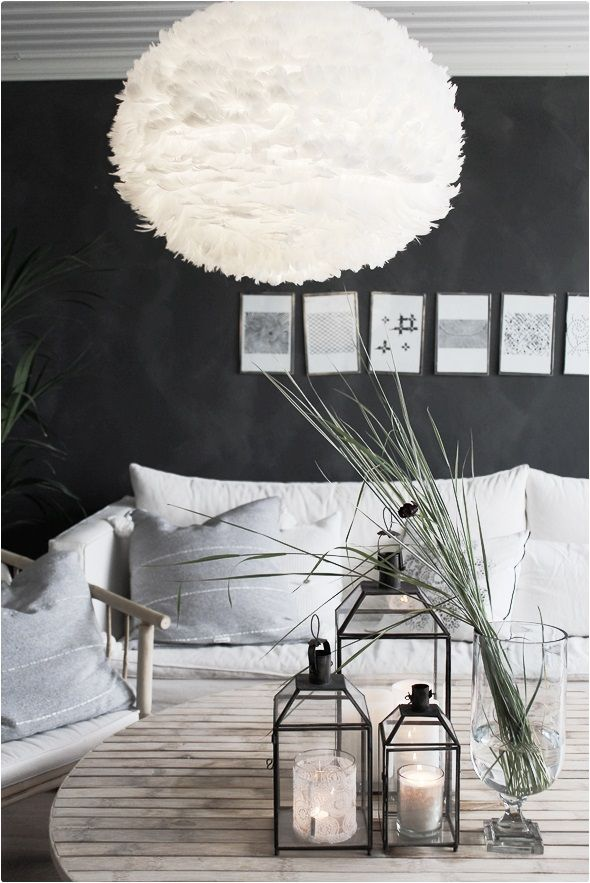 Lanterns on the coffee table with tall grass in a vase, and photo arrangement on black feature wall. So serene. ~w