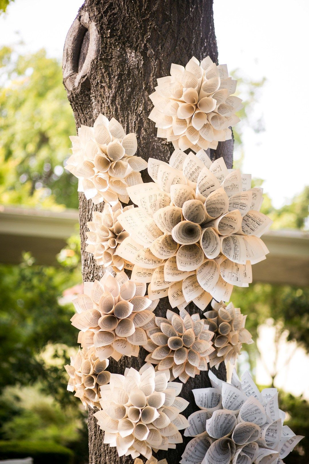 paper flowers made of sheet music attached to a tree trunk at a wedding #paperflowerswedding