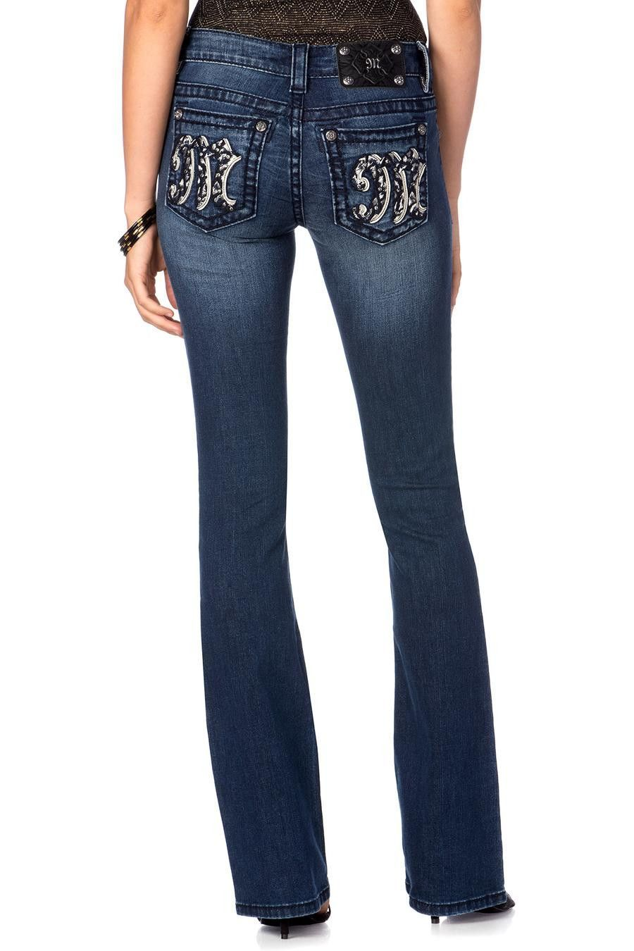 8ce85a38c80 Midrise medium-dark wash boot cut jean with fading and whiskering. Back  pockets feature an embellished M logo. Jean is detailed with large crystal  rivet.