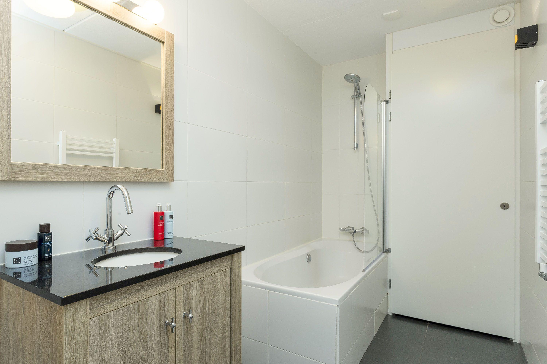 Design Badkamer Arnhem : De badkamer is ingericht met een ligbad met comfortdouche en een