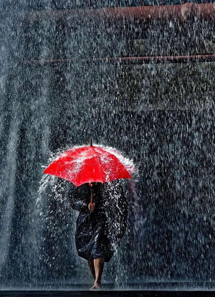 Woman holding a red umbrella & walking in the rain ...