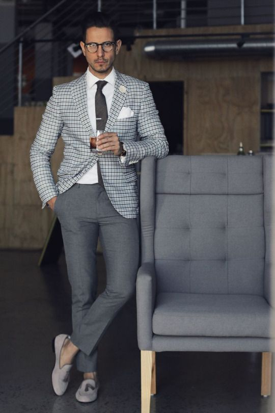 Hot male model wearing grey trousers and a grey jacket over a white shirt leaning on a grey chair