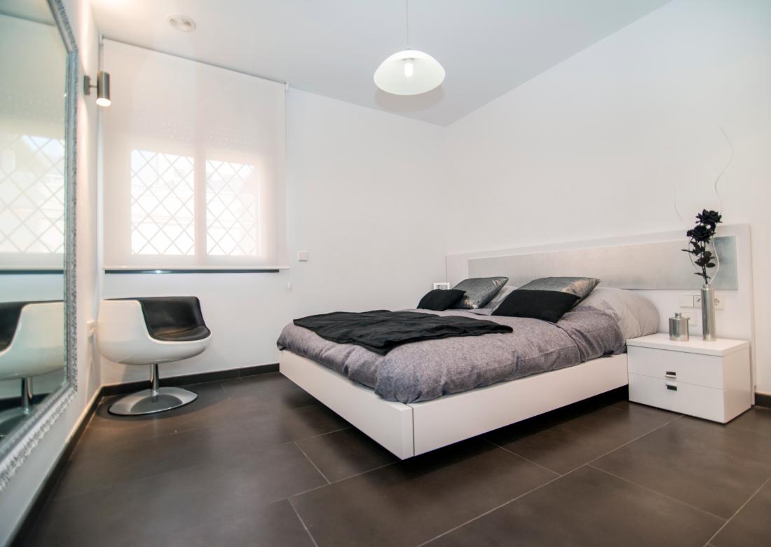 dormitorio de diseño que destaca por el contraste del suelo oscuro