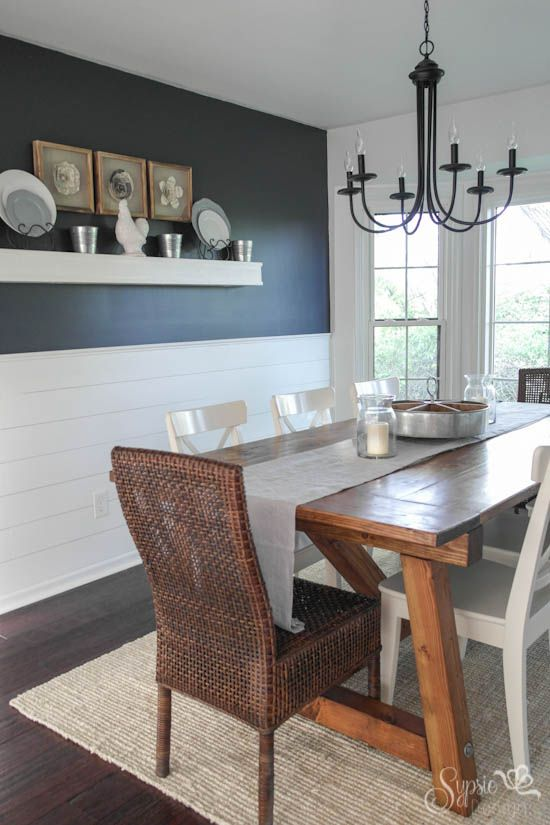 Dining Room with navy and white walls wood white and wicker
