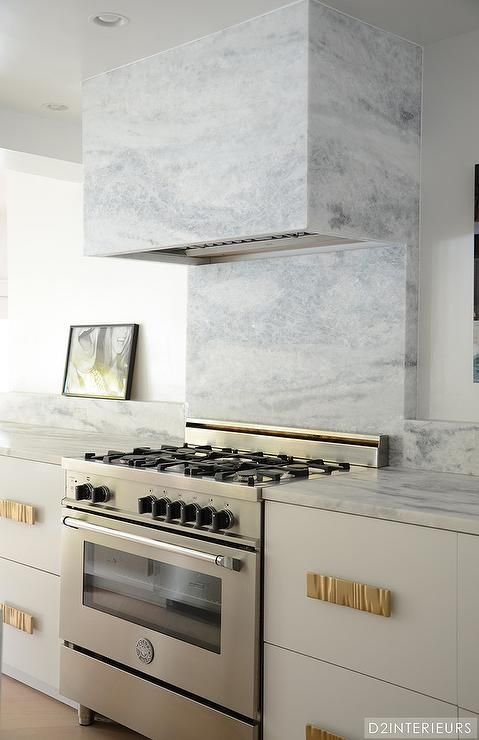 Contemporary kitchen features a white cabinets adorned with gold - contemporary kitchen hoods