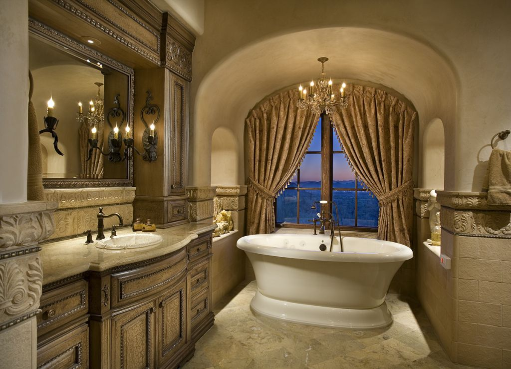 an elegant bathroom bathtub centered in front of window framed out mirror with additional storage travertine marble floors tiles mid way up wall create - Mirror Tile Castle Ideas