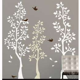 Two large white vinyl spring trees, one small light brown tree decal, and three black bird decals, all on a light brown wall behind a modern couch.